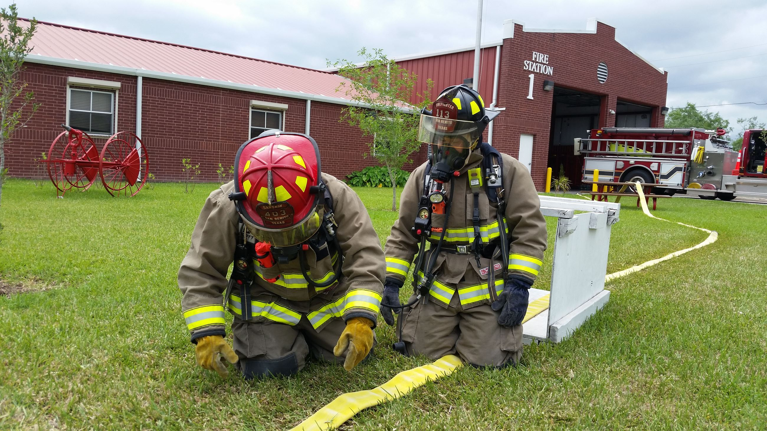Firefighters kneel on the grass with equipment outside a fire station