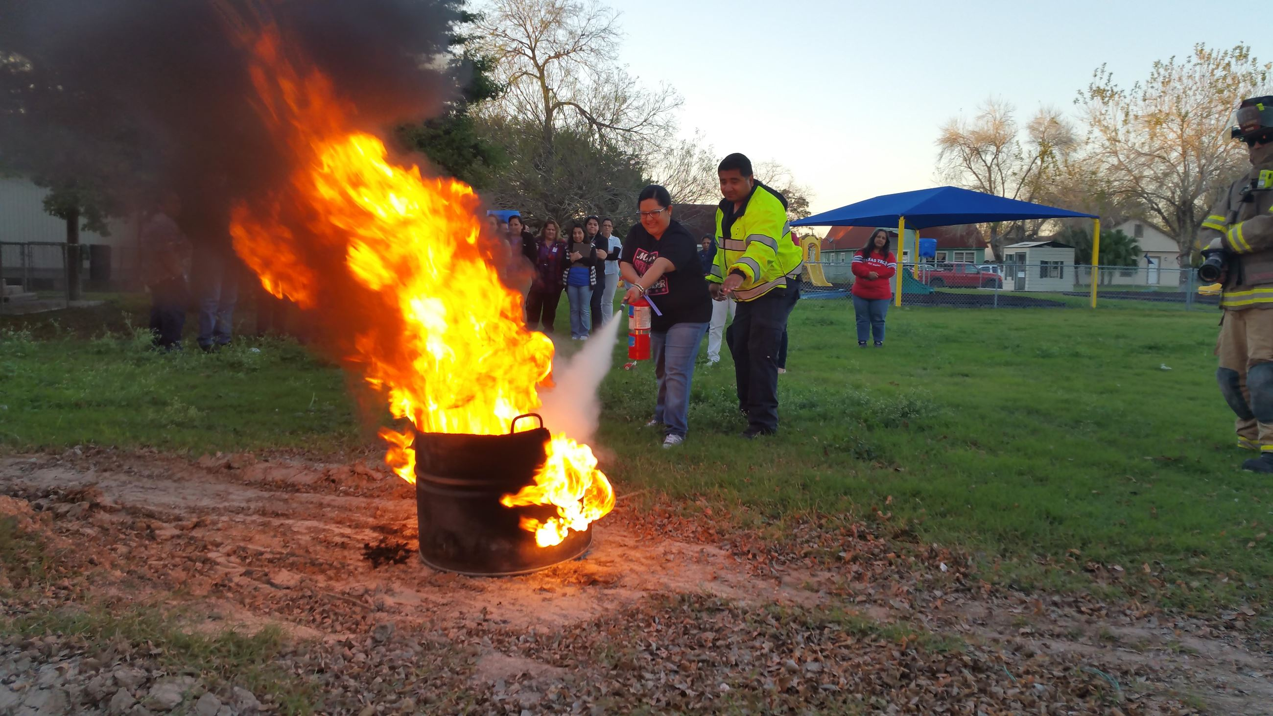 People practice using a fire extinguisher