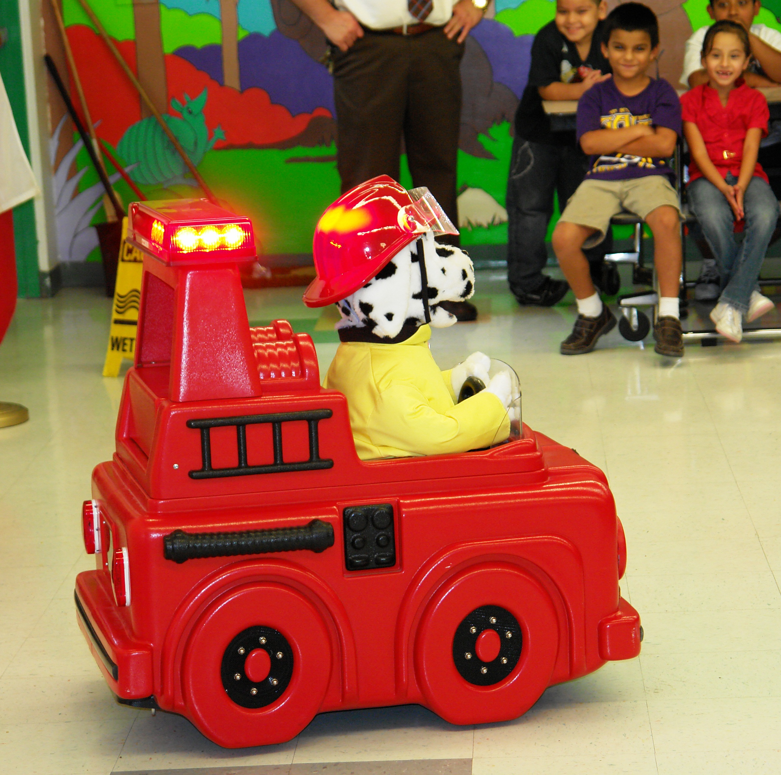 Sparky the stuffed fire dog drives a toy fire truck