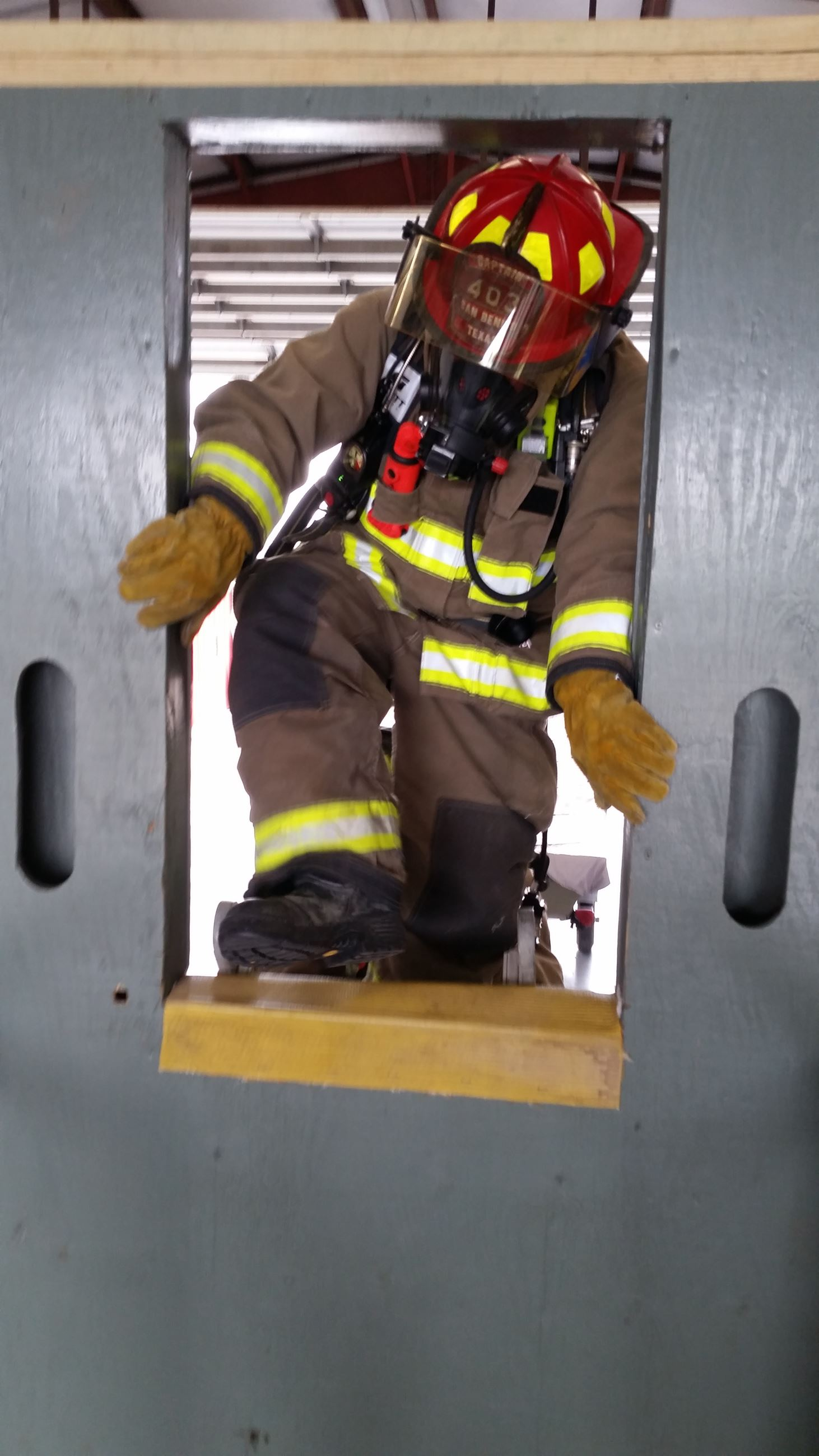 A firefighter climbs through an entry
